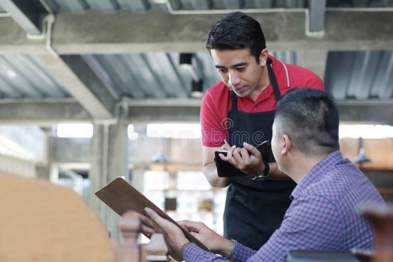 Красивый азиатский мужской официант пишет заказы на тетради с ручкой от costumers на кафе в предпосылке стоковые фото