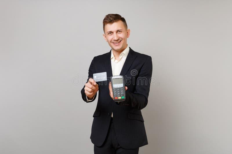 Красивый бизнесмен держа беспроводной современный терминал оплаты банка для обработки и для того чтобы приобрести черноты выплат  стоковое фото rf