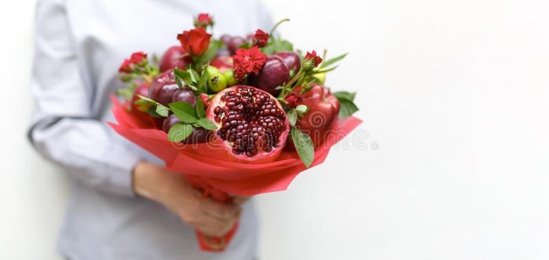 Красивый букет состоя из гранатового дерева, яблок, виноградин, слив и роз шарлаха в руках женщины на белой предпосылке стоковые фото