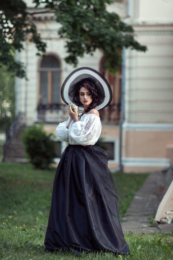 Красивый брюнет в большой черно-белой шляпе стоковые фото