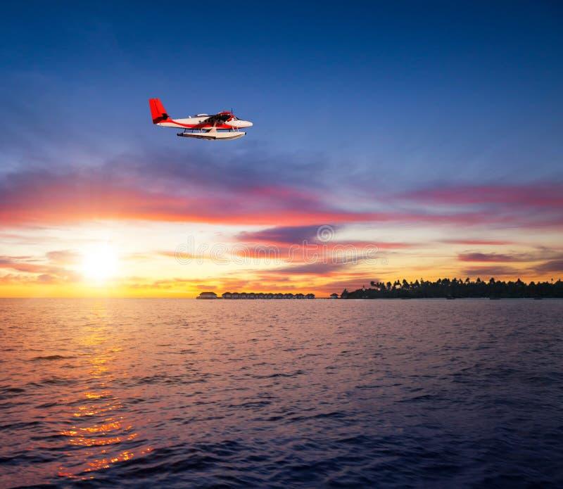 Красивый заход солнца на курорте Мальдивов с гидросамолетом стоковые изображения rf