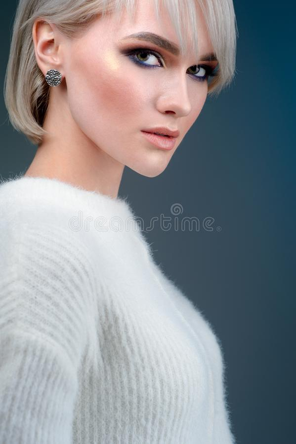 Красивый конец стороны женщины вверх по портрету молодой блондинкы в студии на голубой предпосылке стоковые фото