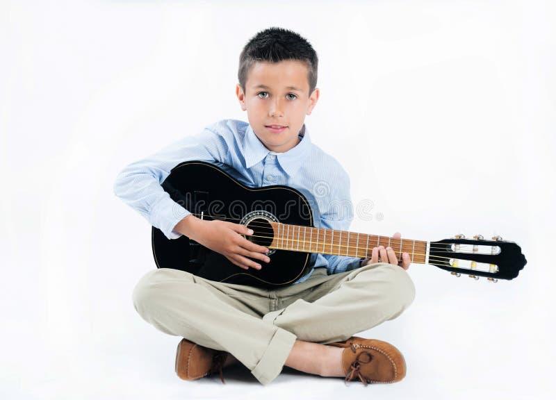 Красивый мальчик брюнета играя гитару на белой изолированной предпосылке стоковое изображение rf