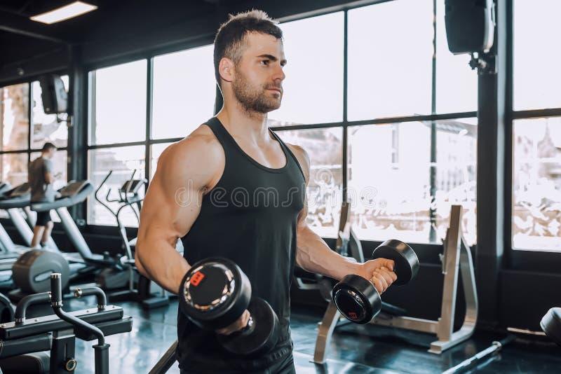 Красивый мышечный человек разрабатывая на спортзале стоковое изображение rf