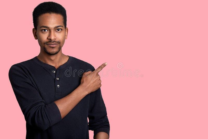 Красивый молодой африканский человек одевает черную рубашку, пункты в сторону с его правой рукой Хороший выглядеть мужской показы стоковая фотография rf