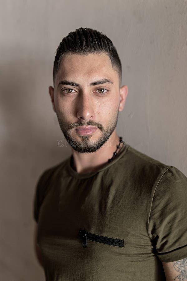Красивый молодой человек со стильным стилем причесок и стойки бороды стерни на предпосылке стены стоковое изображение rf