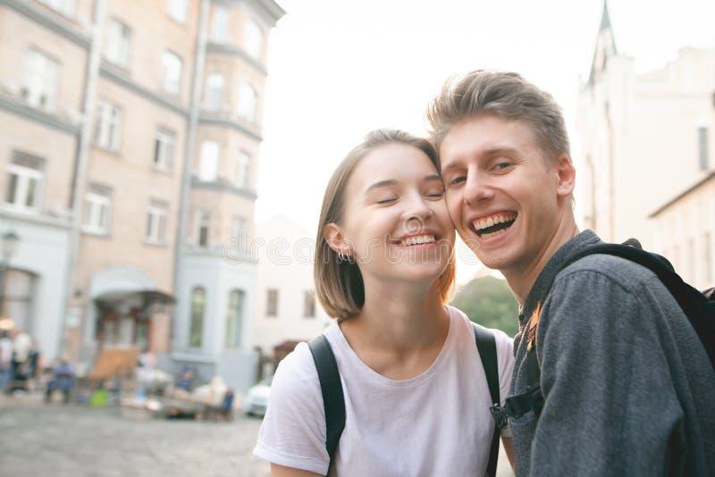 Красивый парень и девушка усмехаясь на заходе солнца и смотря камеру Положительные пары в портрете любов на открытом воздухе стоковое изображение