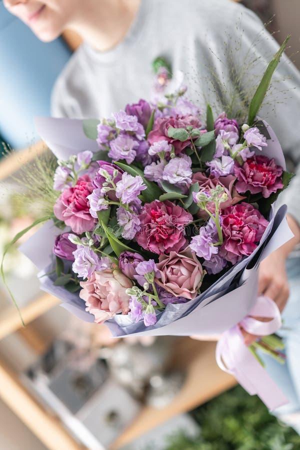 Красивый свежий отрезанный букет смешанных цветков в руке женщины работа флориста на цветочном магазине 9 тюльпанов весны настрое стоковые изображения