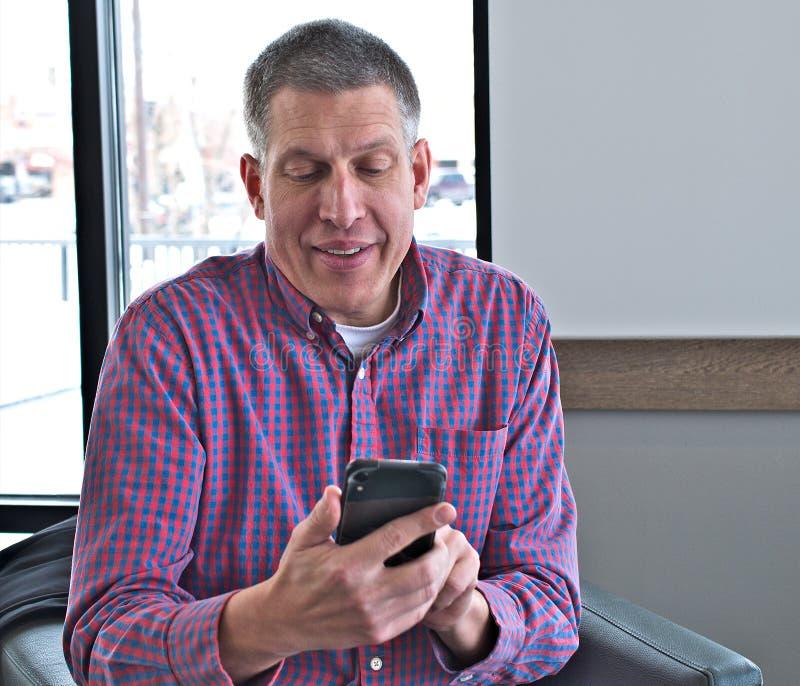 Красивый средний достигший возраста человек в случайных одеждах использует умный мобильный сотовый телефон стоковая фотография