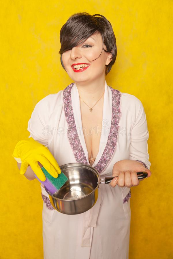 Красивый яркий брюнет в купальном халате держит лоток и губку для моя блюд домохозяйка молодой женщины на желтом backgr студии стоковое фото