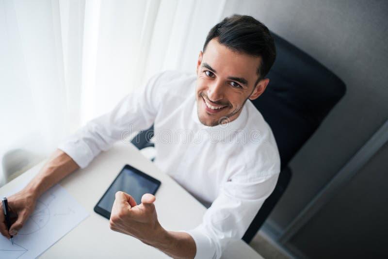 Красивый усмехаясь бизнесмен работая с прибором, устройство в офисе, сидящ на стуле и взгляде на камере стоковая фотография rf