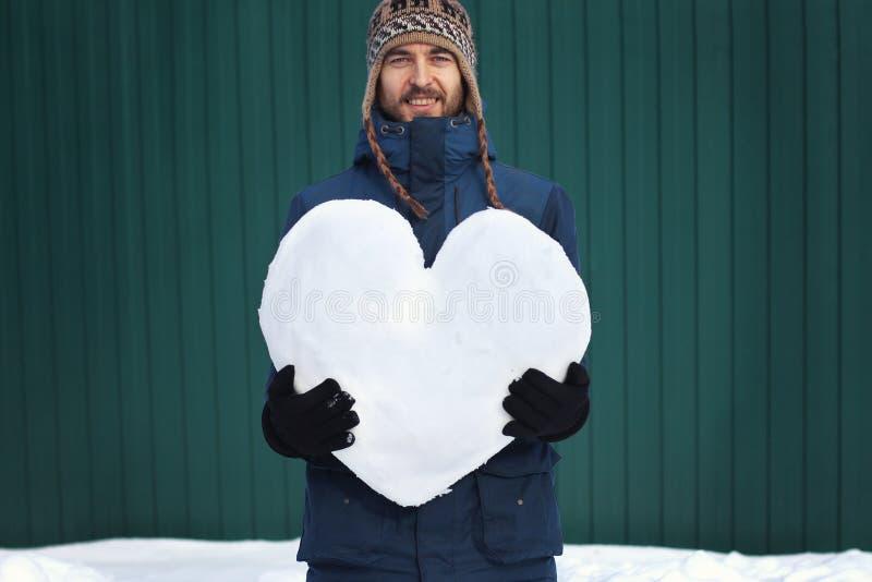 Красивый усмехаясь бородатый человек хипстера в одеждах зимы держа большое сердце сделанный снега, на зеленой предпосылке стены в стоковая фотография rf