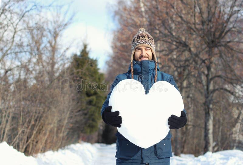 Красивый усмехаясь бородатый человек хипстера держа большое сердце сделанный снега, стоящ на снежной дороге в парке зимы всход вл стоковые изображения rf