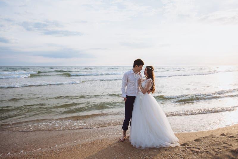 Красивое молодое справедливое marriied положение пар на пляже океана Новобрачные тратят время совместно, обнимают и целуют стоковые изображения