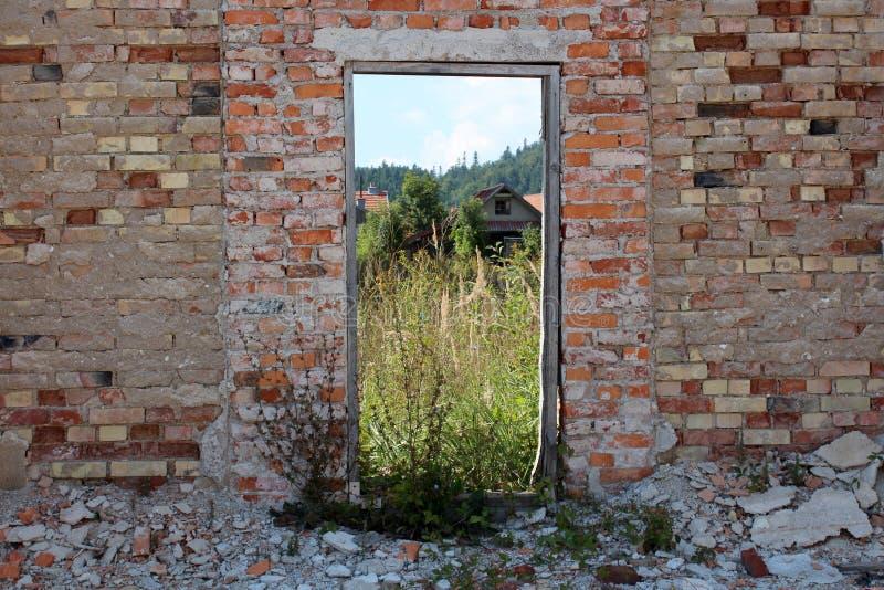 Красная кирпичная стена руин дома с деревянной рамкой вместо деревянных дверей теперь служа как картинная рамка для домов и высок стоковое фото