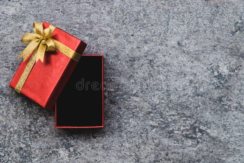 Красная подарочная коробка и золотой смычок который открыт, установленный на серой каменной таблице стоковые изображения