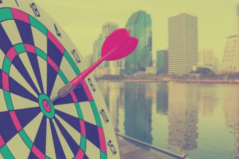 Красная стрелка дротика на dartboard цели с запачканной предпосылкой города стоковая фотография rf
