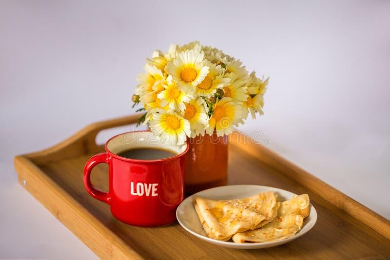 """Красная чашка со словом """"любовью """"с горячими кофе/чаем, букетом маргариток и блинчиками с медом на деревянном подносе стоковое изображение rf"""