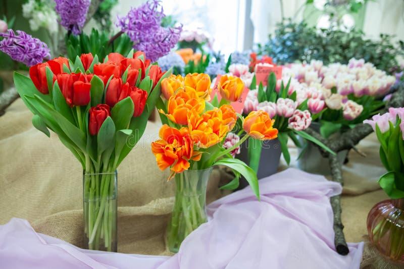 Красные и оранжевые тюльпаны в вазах, выставке цветов, предпосылке лета весны, стоковые фотографии rf