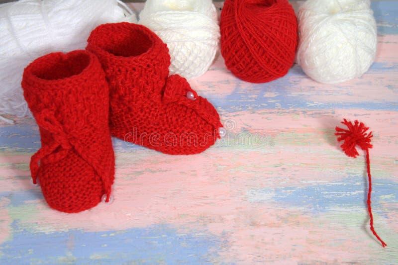 Красные связанные добычи младенца, красные и белые шарики пряжи шерстей для вязать и красного помпона пряжи на пинке - голубой пр стоковое изображение rf