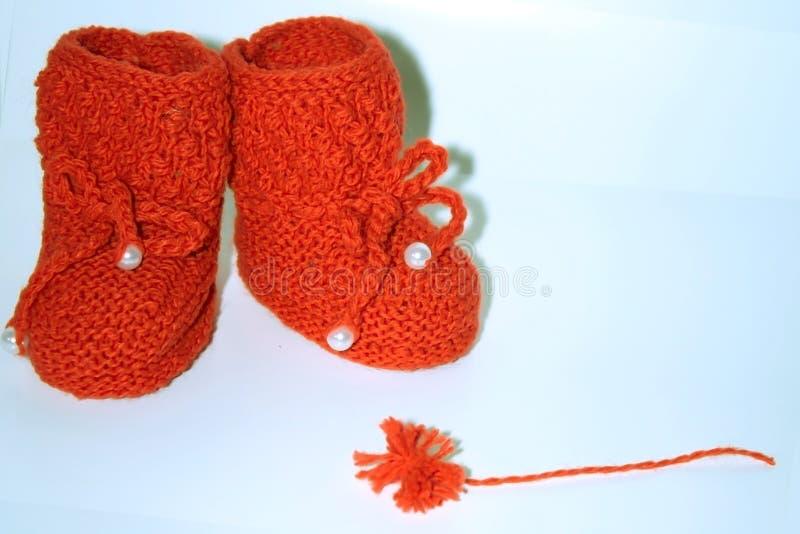 Красные связанные добычи младенца и красный помпон пряжи на белой предпосылке стоковые фотографии rf