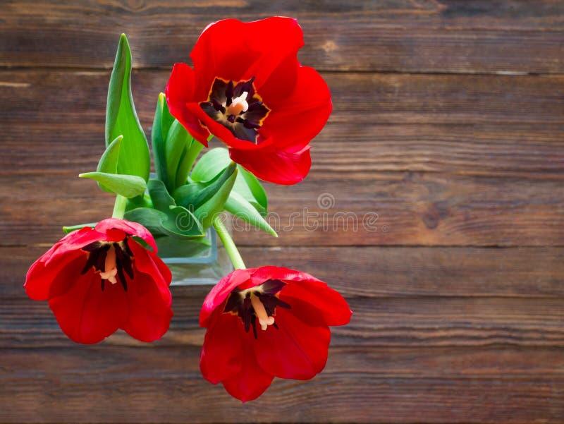 Красный букет тюльпанов над предпосылкой деревянного стола с космосом экземпляра стоковая фотография rf