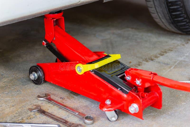 Красный инструмент поднимает автомобиль домкратом подъема для проверки ремонта стоковые изображения rf