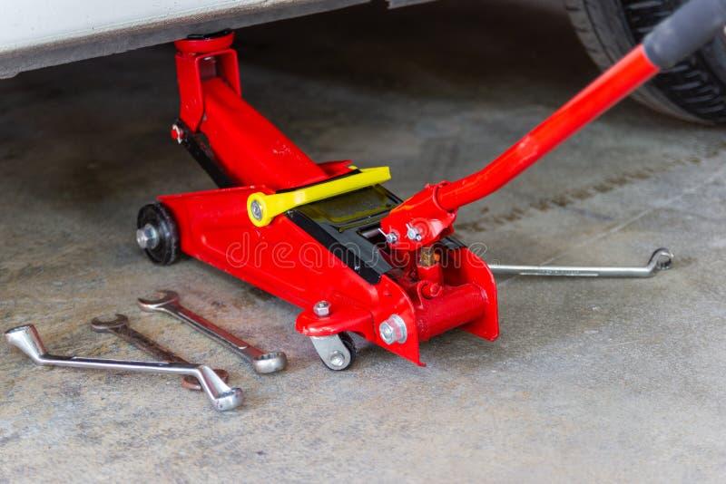 Красный инструмент поднимает автомобиль домкратом подъема для проверки ремонта стоковые фотографии rf