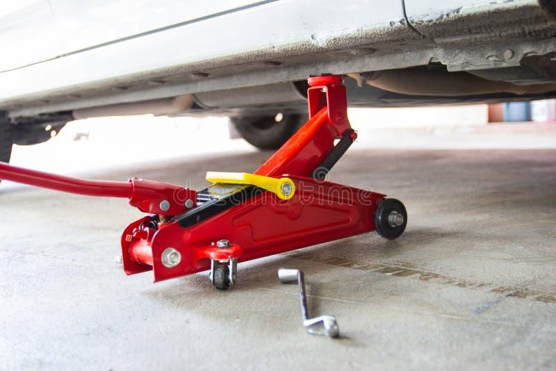 Красный инструмент поднимает автомобиль домкратом подъема для обслуживания проверки ремонта стоковые изображения rf