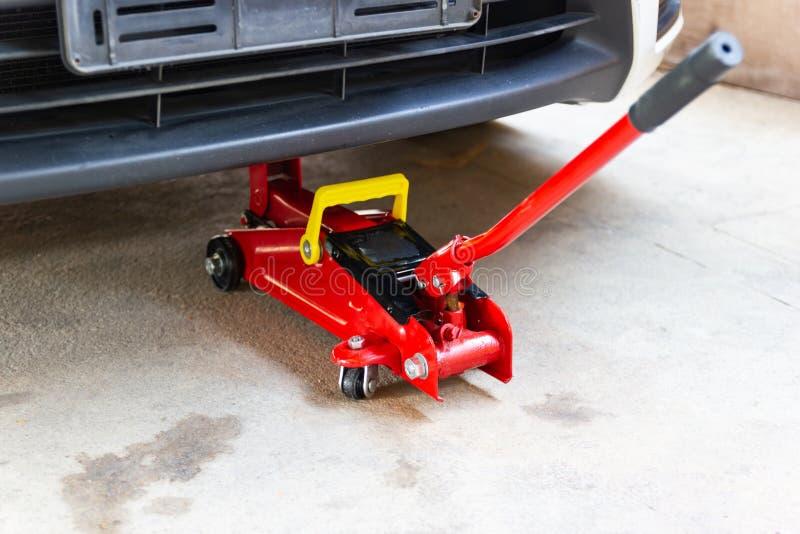 Красный инструмент поднимает автомобиль домкратом подъема для проверки ремонта стоковое изображение rf