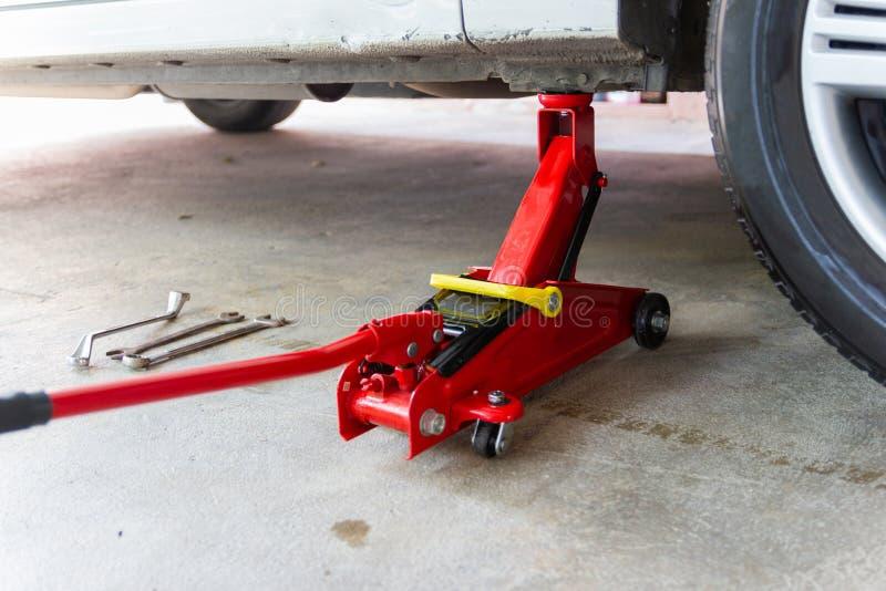 Красный инструмент поднимает автомобиль домкратом подъема для обслуживания проверки ремонта стоковое фото