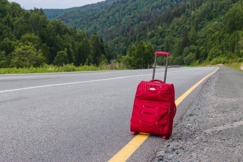 Красный чемодан стоит на дороге стоковые фотографии rf