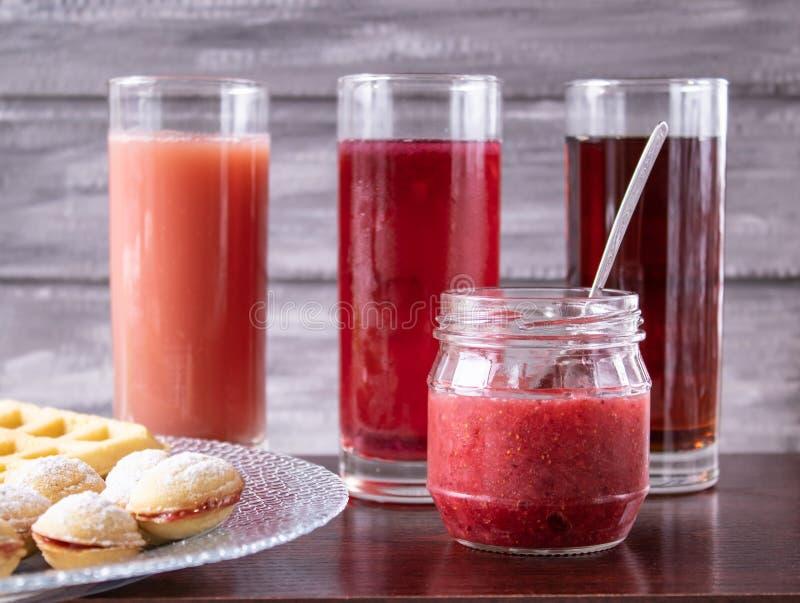 Красный сок в стекле рядом с шаром печений и небольшого опарника варенья стоковые изображения rf