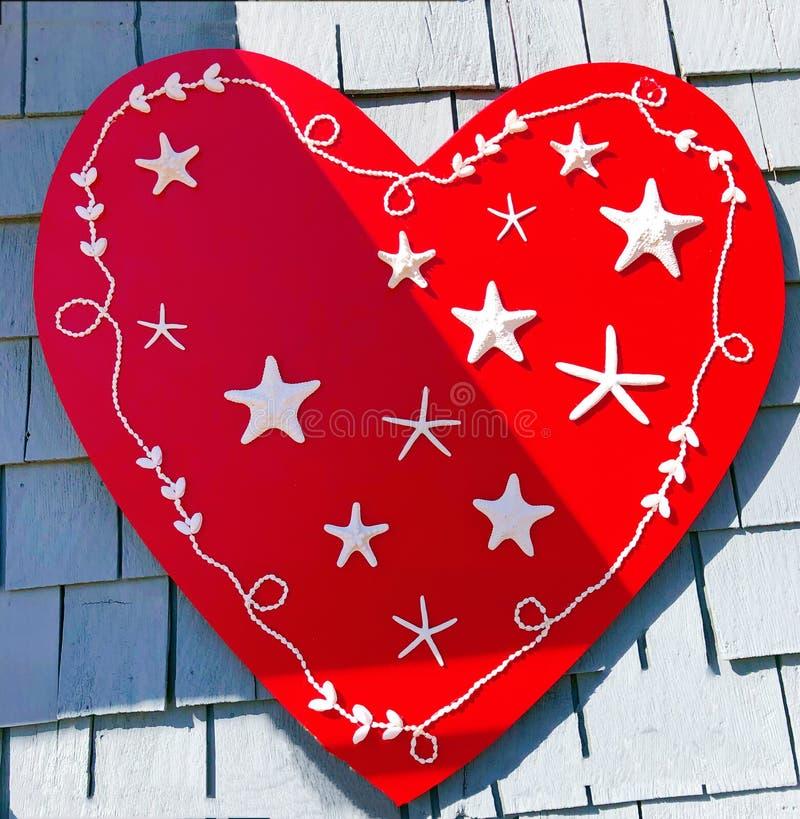Красное сердце с белыми морскими звёздами стоковое изображение