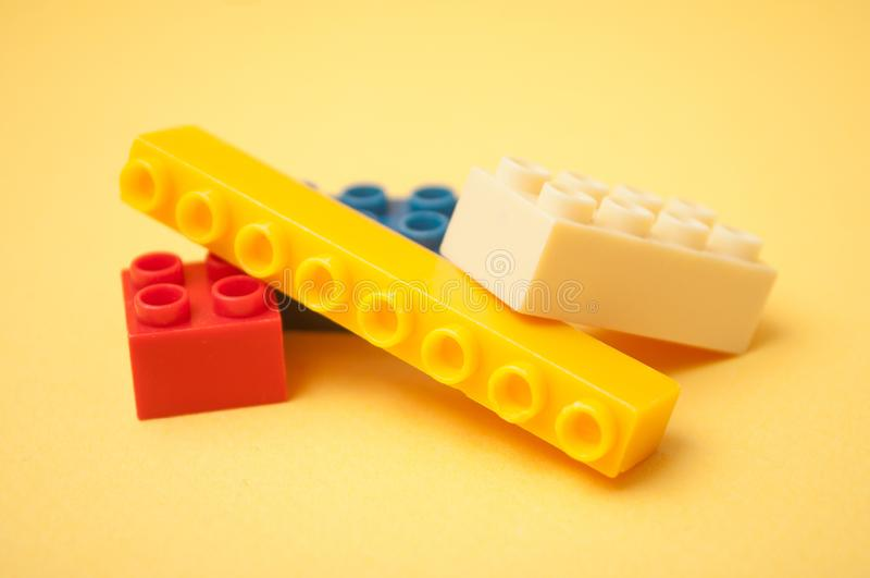 Красочная пластиковая конструкция кирпичей на желтой предпосылке стоковая фотография