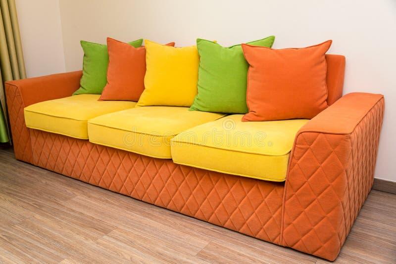 Красочная софа желт-апельсина с зелеными, желтыми и оранжевыми подушками стоковое фото