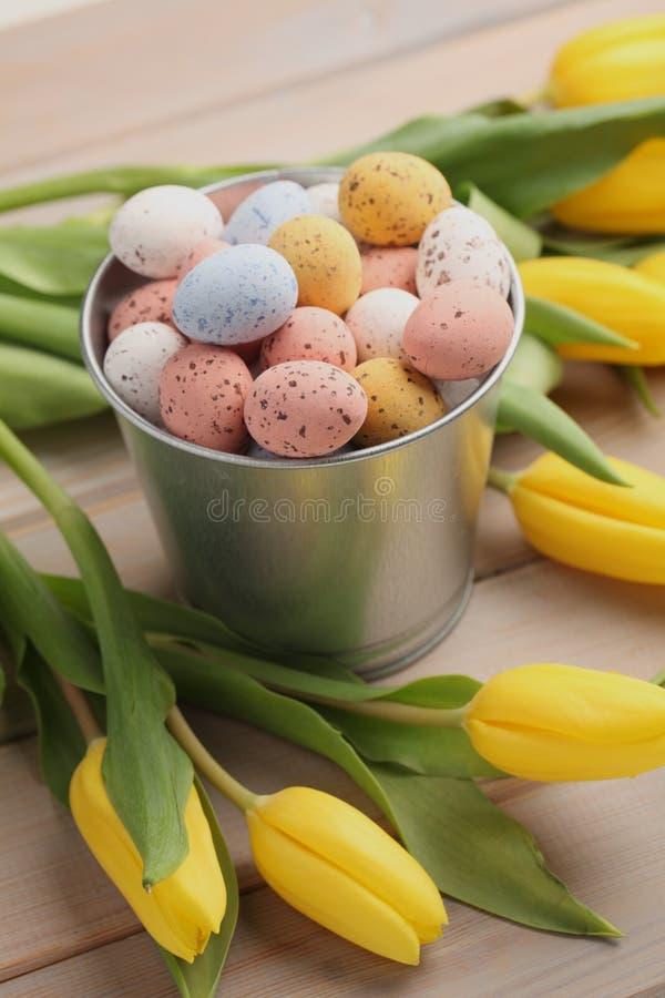 Красочные яйца конфеты пасхи с желтыми тюльпанами стоковая фотография