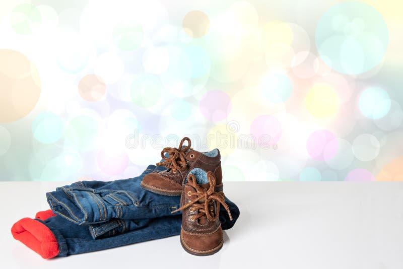 Красочные одежды джинсов детей Модные красные выровнянные thermojeans и ультрамодная пара голубых тапок на яркой таблице сверх стоковое фото rf