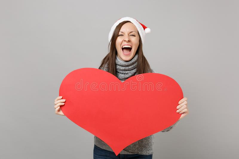 Кричащая девушка Санта в серой шляпе рождества шарфа свитера держа пустое пустое красное сердце изолированный на серой предпосылк стоковые изображения