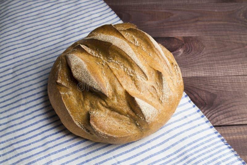 Круглый свежий домодельный хлеб на деревянном столе с striped салфеткой, взгляд сверху стоковая фотография rf