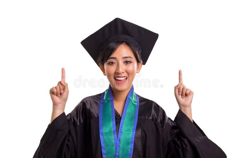 Крупный план привлекательной девушки студента в ее постдипломном костюме указывая оба пальца рук вверх стоковое фото