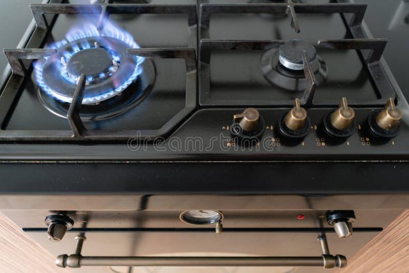 Крупный план снятый голубого огня от hob отечественной кухни Плита газа с горящим газом пропана пламен стоковое изображение rf