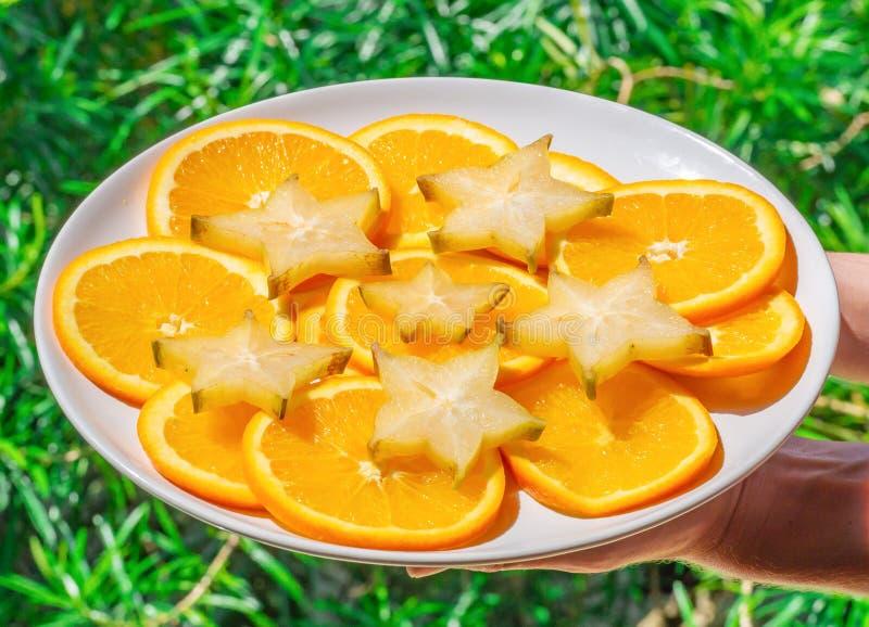 Крупный план снятый рук держа плиту со звездами карамболы и оранжевыми кусками, концом вверх Здоровая и вегетарианская концепция  стоковые изображения