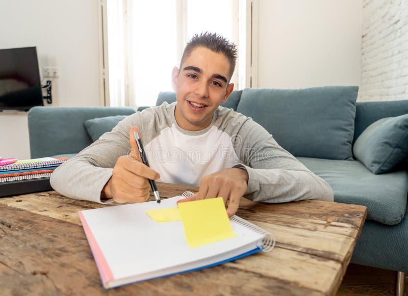 Крупный план счастливый, жизнерадостный изучать молодого человека, работая в домашней работе Учить от книг дома стоковое фото