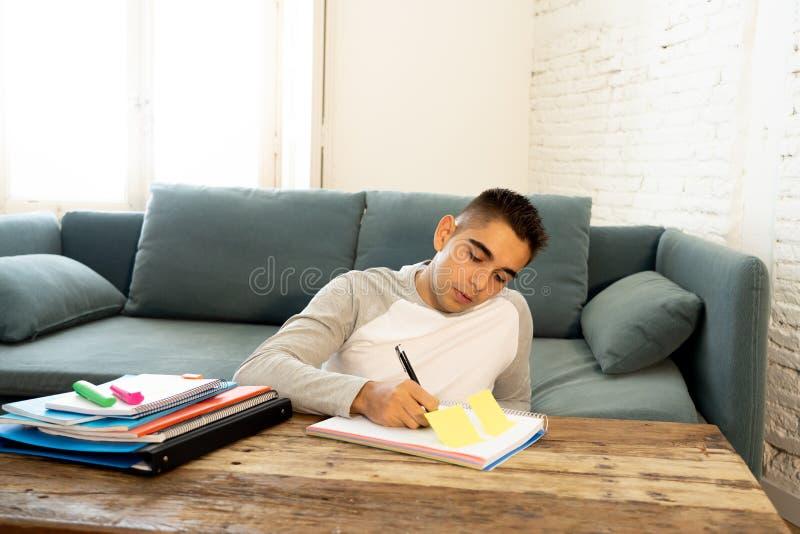 Крупный план счастливый, жизнерадостный изучать молодого человека, работая в домашней работе Учить от книг дома стоковые изображения
