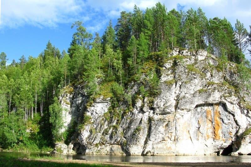 Крутая скала над рекой с лесом на верхней части Яркий солнечный день, спокойная подача воды стоковая фотография