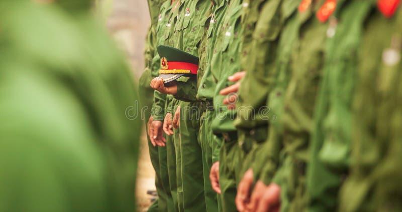 Крышка officer's армии Вьетнама с красной звездой в руке молодого въетнамского солдата в ряд, во время программы посещения сайт стоковые фото