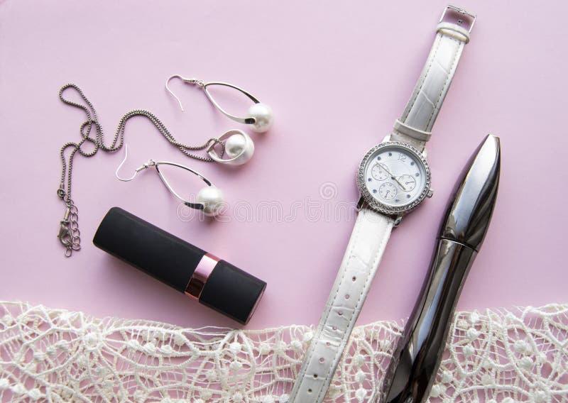 Коллаж аксессуаров плоских женщин положения со стильными дозорами, серьгами и шкентелем с белыми жемчугами, губной помадой, тушью стоковая фотография