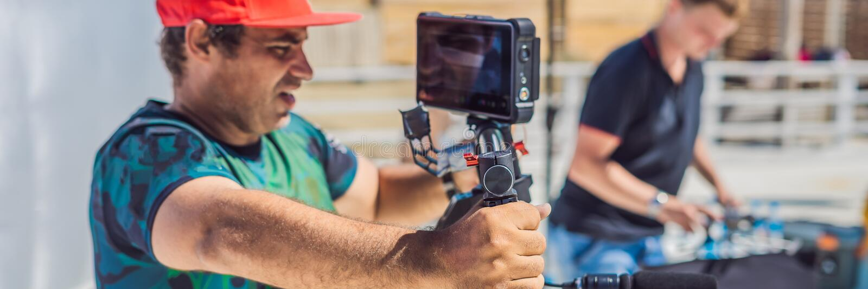 Команда продукции на коммерчески видео- всходе Оператор Steadicam использует стабилизатор и кино-степень камеры 3 осей стоковое фото rf