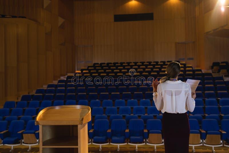 Коммерсантка практикуя и уча сценарий пока стоящ в аудитории стоковое фото rf